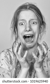 Close up portrait young woman desperate and scared  looking terrorized and horrified screaming in primal fear emotion face expression