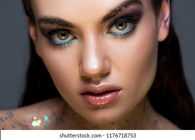 close up portrait of young woman with fashionable makeup, isolated on grey