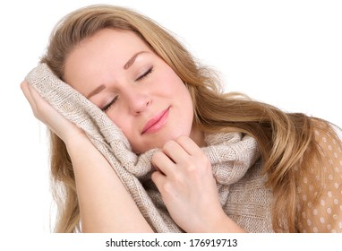 Close up portrait of a young woman feeling soft sweater against face