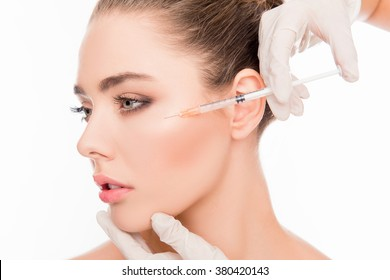 Close up portrait of young  woman getting cosmetic injection with  syringe
