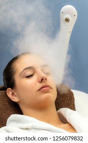 Close up portrait of young woman having thermal steam treatment in spa. Girl with eyes closed in white gown laying on couch.