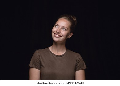 Close up portrait of young woman isolated on black studio background. Photoshot of real emotions of female model. Dreaming and smiling, hopeful and happy. Facial expression, human emotions concept.