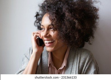 Close up portrait of a young woman laughing and talking on mobile phone