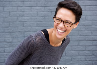 Close up portrait of a young woman laughing with glasses against gray background