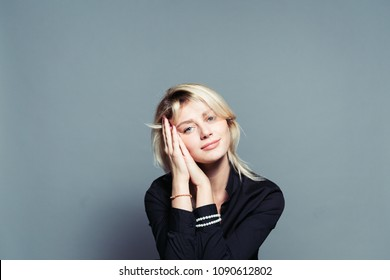 Close up portrait of a young woman, looking to the camera, hands together near face, against a plain studio background