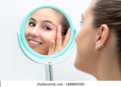 Close up portrait of young woman looking in mirror at herself. Girl touching skin with hands.