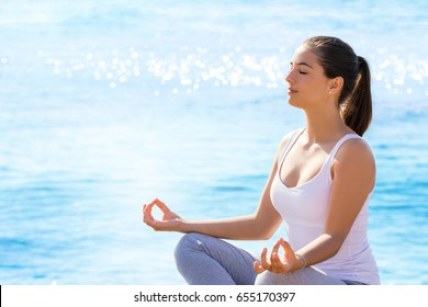 Close up portrait of young woman meditating in yoga position outdoors. Girl in casual wear sitting against blue sea background with sun reflecting on water surface.