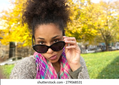 Close up portrait of a young woman peeking over sunglasses