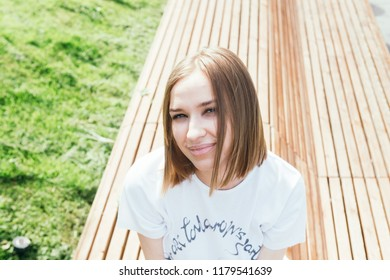 Close up portrait of a young woman posing on the bench in a city park in the centre of Moscow