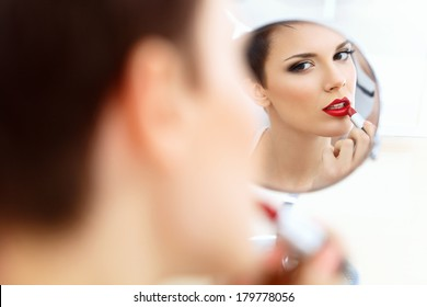 Close up Portrait of Young Woman With Red Lips. Beautiful Woman Doing Daily Makeup. Lipstick applying