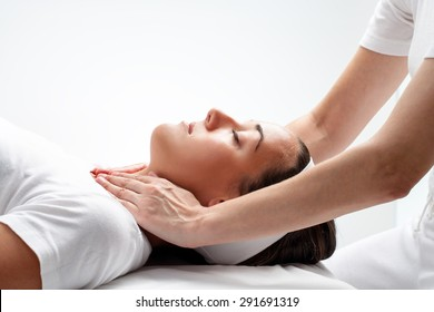 Close up portrait of young woman at reiki session.Therapist touching woman neck wit hands.