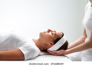 Close up portrait of young Woman relaxing with eyes closed at reiki session.Girls head resting on therapist hands.
