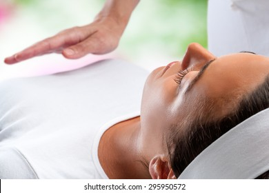 Close up portrait of young woman relaxing at reiki session with therapist hand in background.
