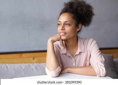Close up portrait of a young woman sitting down and thinking