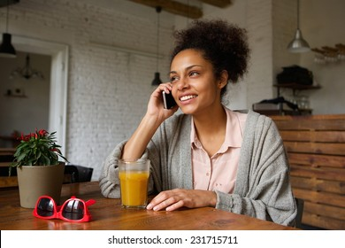 Close up portrait of a young woman smiling and talking on mobile phone