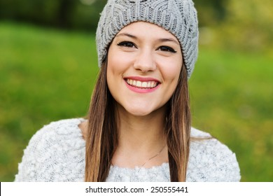 Close up portrait of young woman smiling in a park.