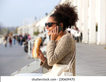 Close up portrait of a young woman talking on mobile phone and eating outdoors