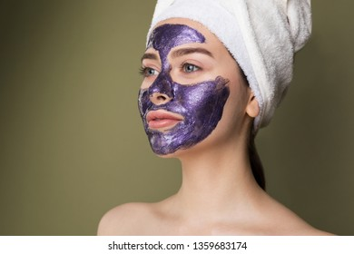 Close up portrait of young woman with towel on her head after shower apply purple moisturizing mask on face isolated on green background