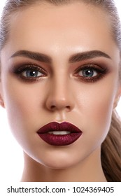 Close up portrait of young woman with wine red lips and bronze smokey eyes. Modern fashion make up. Studio shot