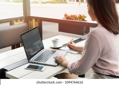 Close up portrait of a young woman working on laptop and writing, coffee on the table.