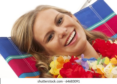 Close up portrait of young woman with yellow bikini and red lei lying in beach chair