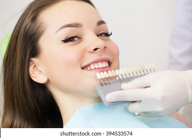 Close up portrait of Young women in dentist chair, Check and select the color of the teeth. Dentist makes the process of treatment in dental clinic office.Dentist