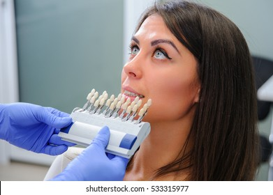 Close up portrait of Young women in dentist chair, Check and select the color of the teeth.