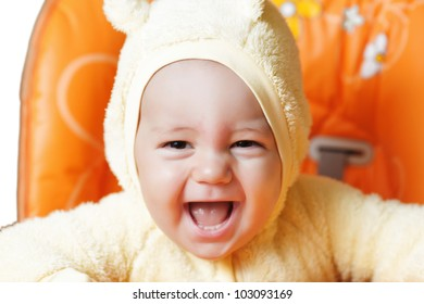 close up portraiy of baby boy smiles his widest smile ever as he laughs while sitting in his highchair