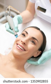 Close up of positive dark haired woman smiling and having dermabrasion of her facial skin in professional clinic