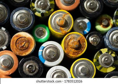 Close up of positive ends of discharged batteries of different sizes and formats, selective focus. Used alkaline battery with corrosion and rust. Hazardous garbage concept