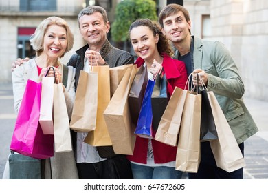 Close up of  positive smiling tourists with purchases on European city street