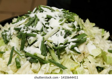 Close up to a pot with sliced cabagge,  chive and suger used to prepare sukiyaki, japanese food recipe.
