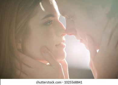 A close up potrait of two belovers looking at each other. They are going to kiss.