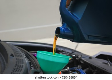 Close up of Pouring fresh oil to car engine