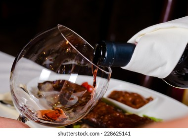 Close Up of Pouring Red Wine into Glass in Restaurant Setting