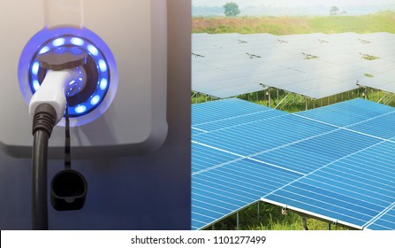 Close up of power supply plugged into an electric car being charged with panel of solar cells generating electricity using solar energy in the background. (Renewable Energy Concept)