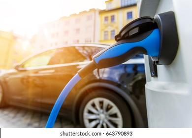 Nahaufnahme des Netzteils, das an ein aufgeladenes Elektroauto angeschlossen ist