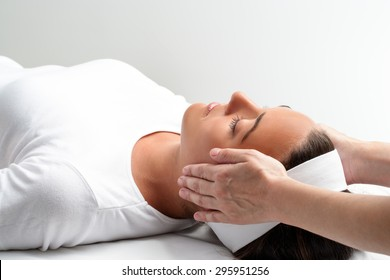 Close up of practitioner doing reiki with hands on young woman. Therapist doing healing treatment with hands next to head.