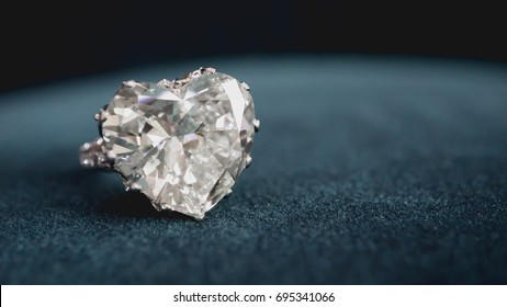 Close up precious heart shape diamond ring with on blue background. soft and selective focus