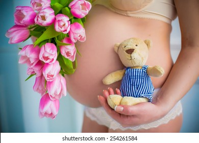 close up of pregnant belly. Spring inspiration with pink flowers tulips and teddy bear