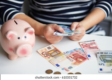 Close up of a pregnant woman behind the desk counting money