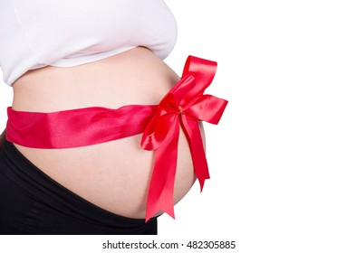 close up pregnant woman with red ribbon gift on belly isolated on white background