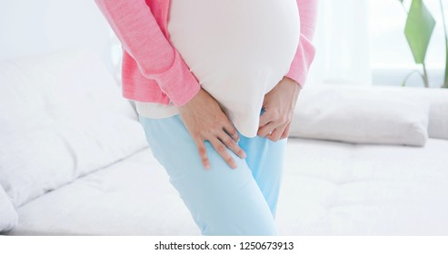 close up of pregnant woman urine urgency at home