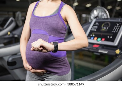 Close up of pregnant woman using smart device for fitness in the gym