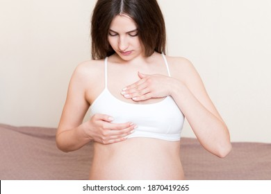Close Up of pregnant women having painful feelings in breast. Woman checking her breast for cancer.