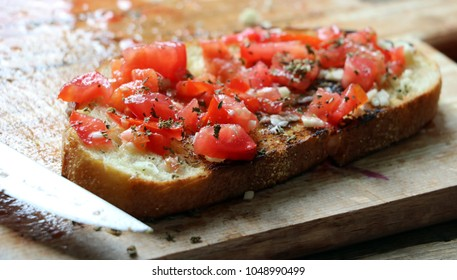 close up preparing bruschetta on a wooden plate