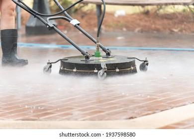 Close up pressure washing brick drive way