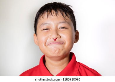 Close up of preteen boy looks sad while having nosebleed in the studio, isolated on white background