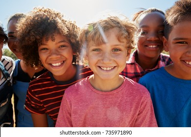 Close up of pre-teen friends in a park smiling to camera
