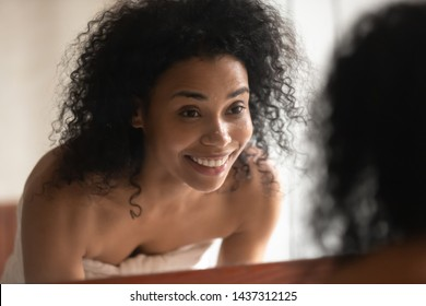Close up pretty 30s woman after shower wrapped in towel look in mirror having toothy smile washing her face perfect skin with water remove make up in bathroom skincare natural beauty treatment concept